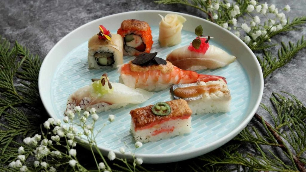 sushi and fish sitting on a plate