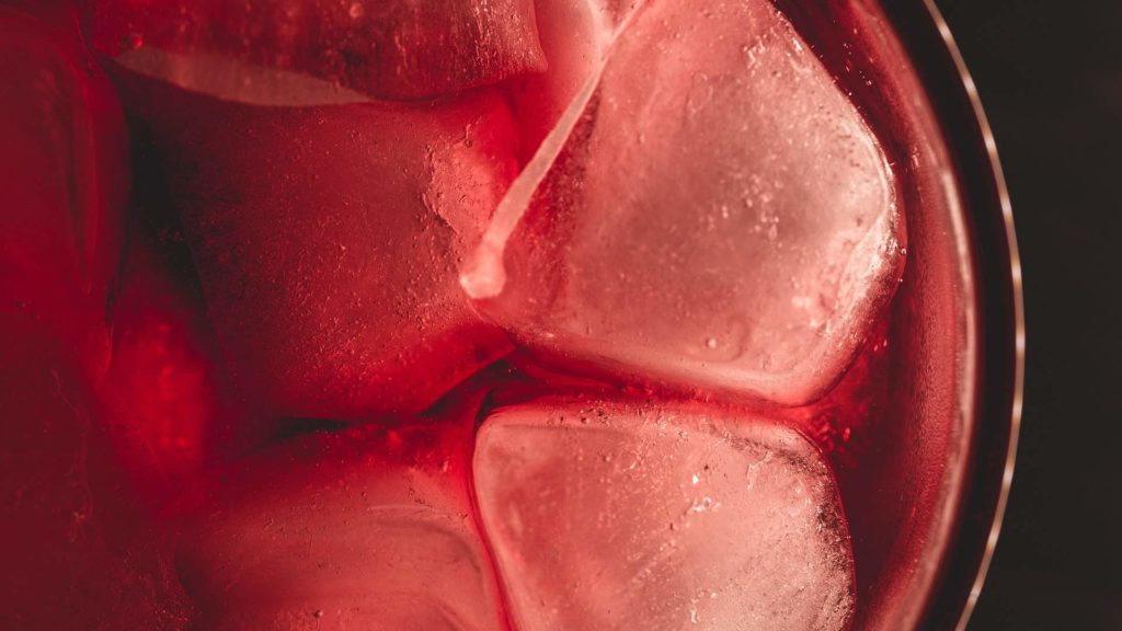 Ice cubes in a cup with red liquid
