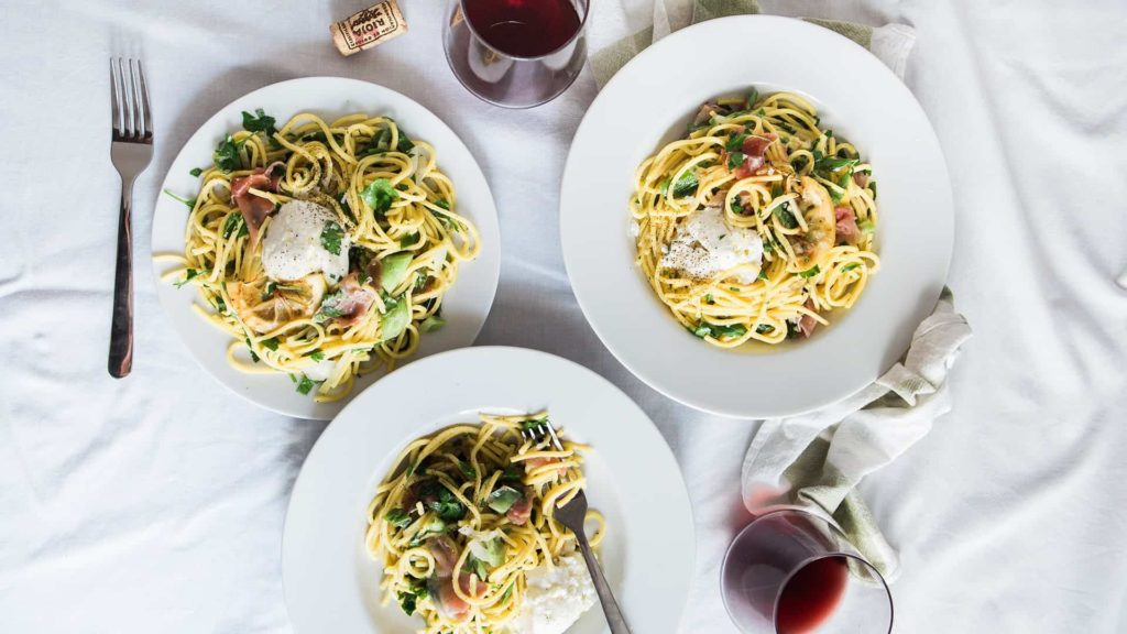 Three plates of pasta sitting on a table