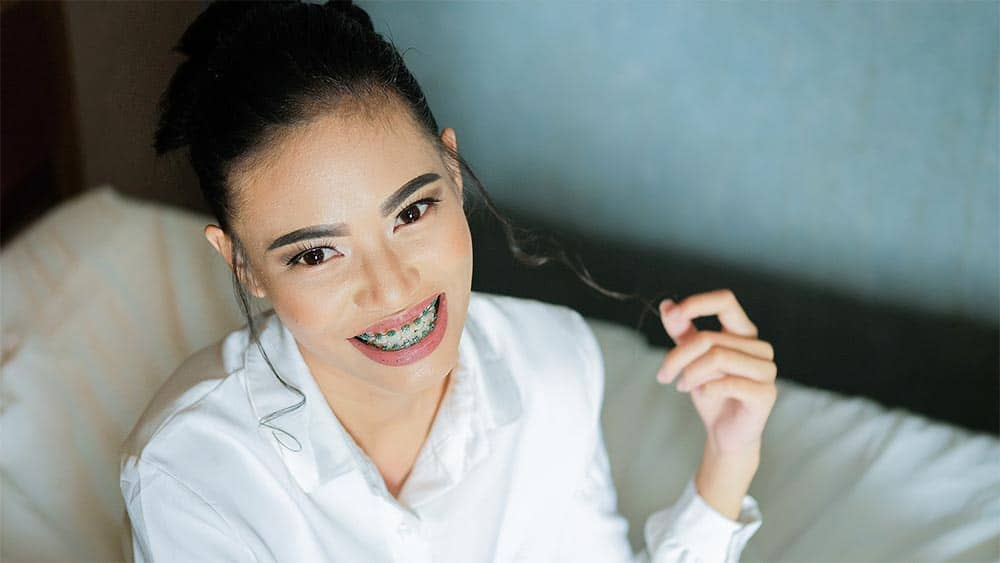 smiling young woman with traditional braces